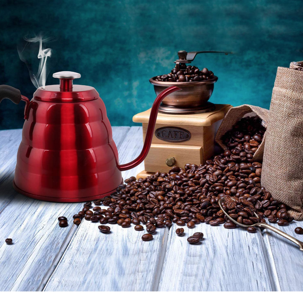 a red gooseneck kettle sitting on a table next to coffee beans
