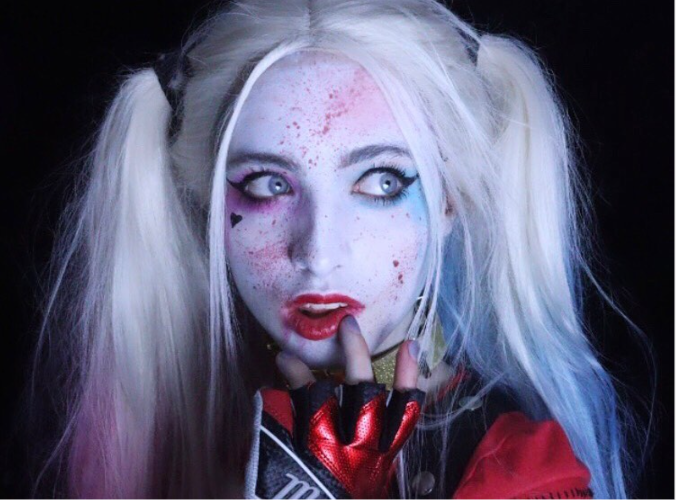 A woman is dressed in white clown makeup and pigtails as part of her Halloween costume.
