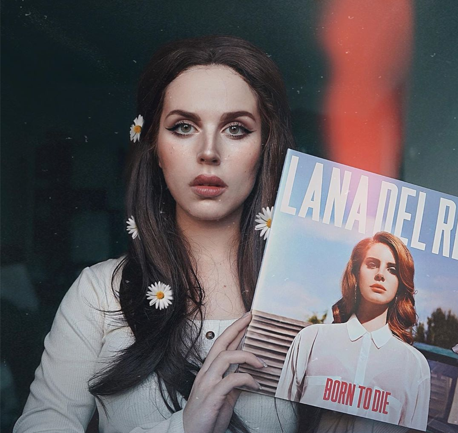 A girl with flowers in her hair and heavy makeup holds a Lana Del Rey album for her costume.