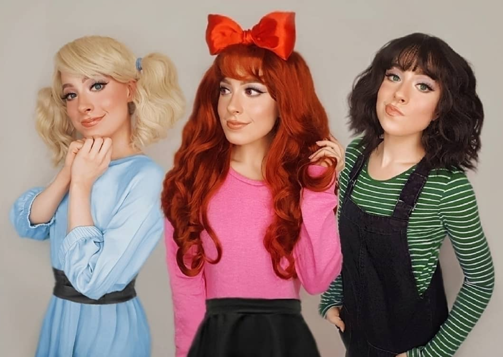 Three girls are dressed in pink and blue and green.