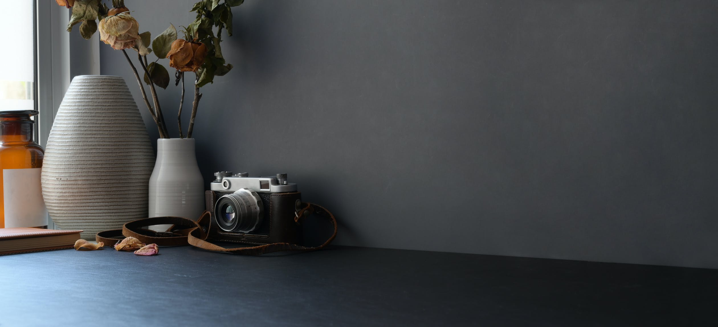 gray wall with a desk, camera, and flower pot