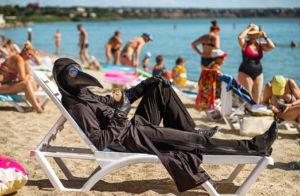 A man in a plague doctor outfit sits on the beach.