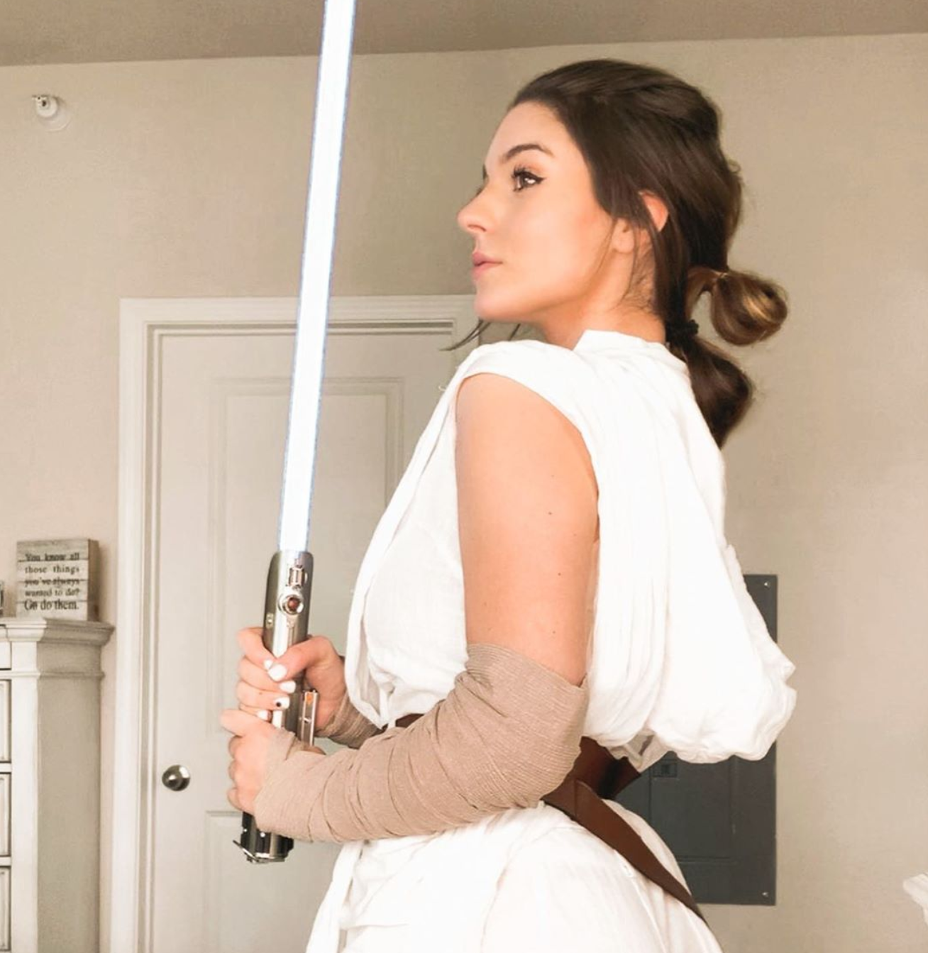 A woman holds a light saber and tied her hair in three buns as part of her costume.