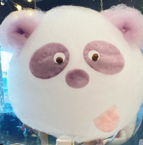 Purple and white cotton candy in the shape of a panda.