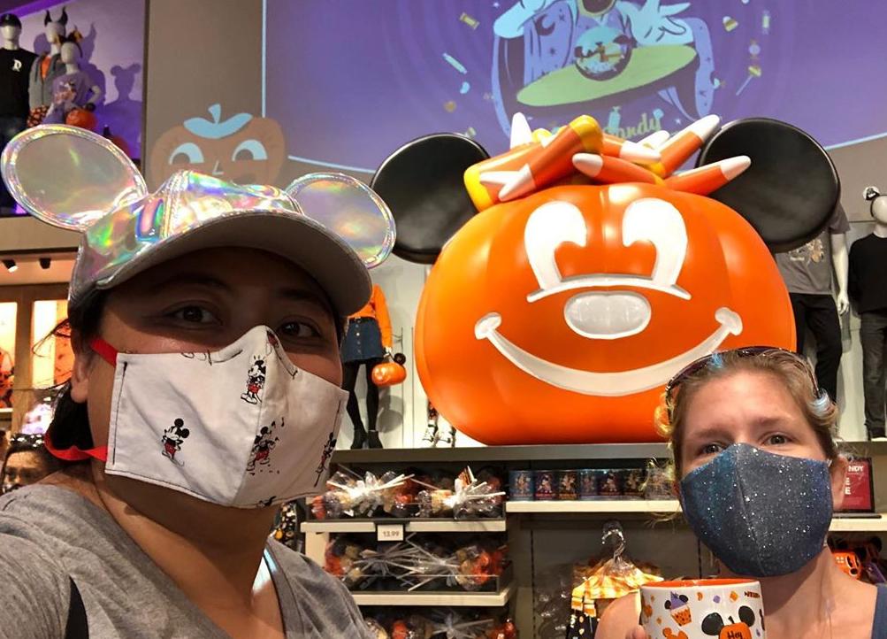 Two women pose in front of Downtown Disney merchandise in OC.