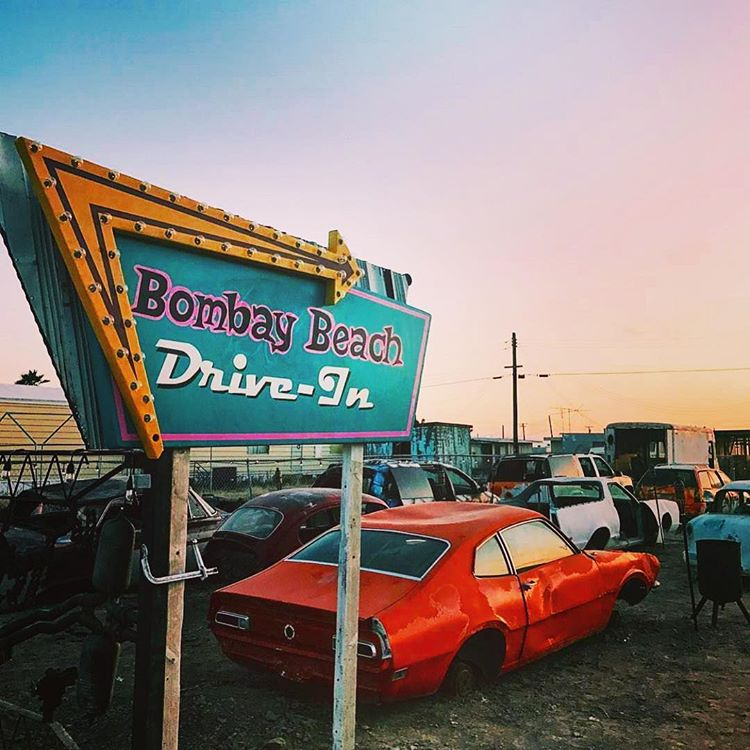 Bombay Beach decaying drive-in with rusted cars at sunset