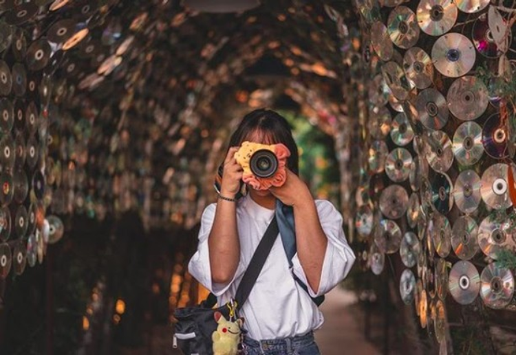 Girl posing in Anti-Mall's tunnel covered with CDs