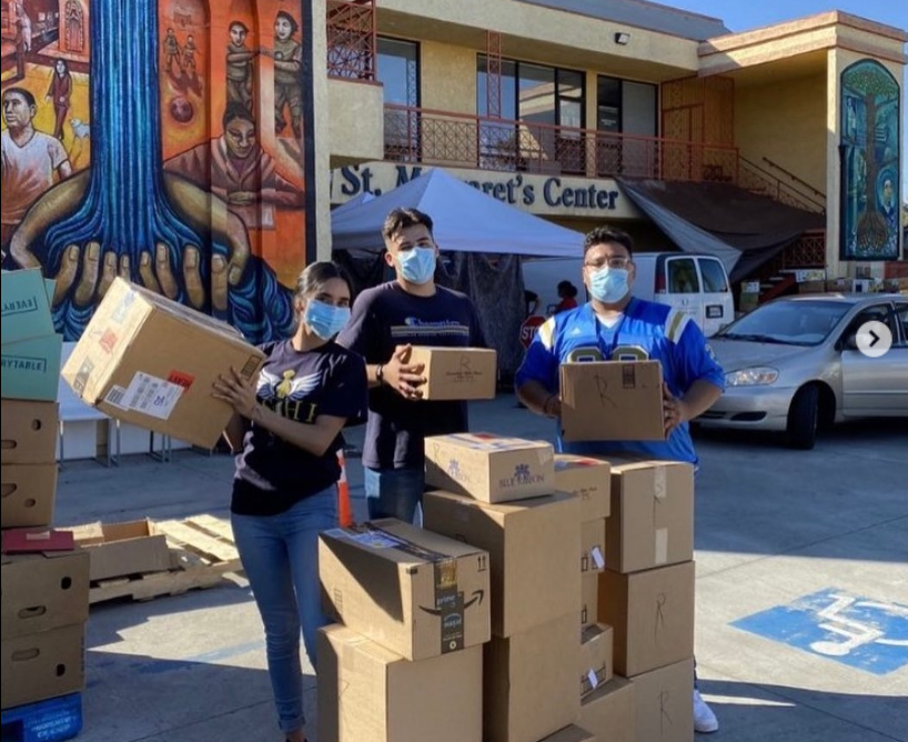Latinx volunteers in LSHP for LCCM picking up boxes in front of St. Margaret's Center.