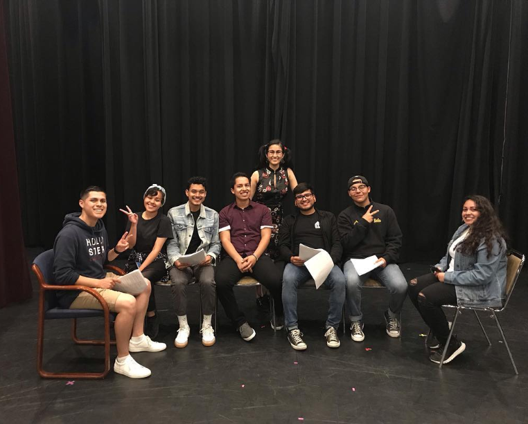 Latinx film students posing on the stage of a theater.
