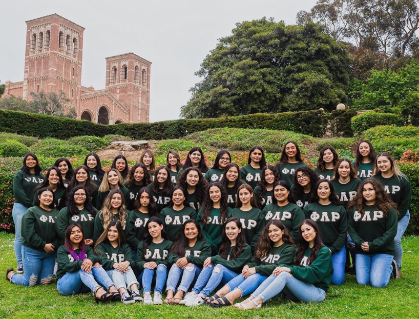 Latinas of Phi Lambda Rho posing in their green shirts on the grass outside of Powel Library.