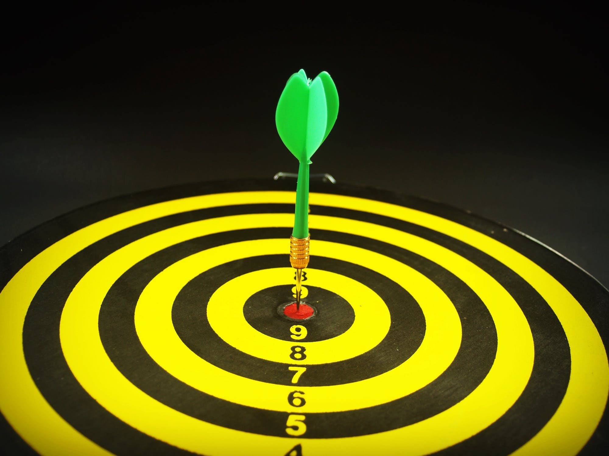 A dart sitting in the center of a target.