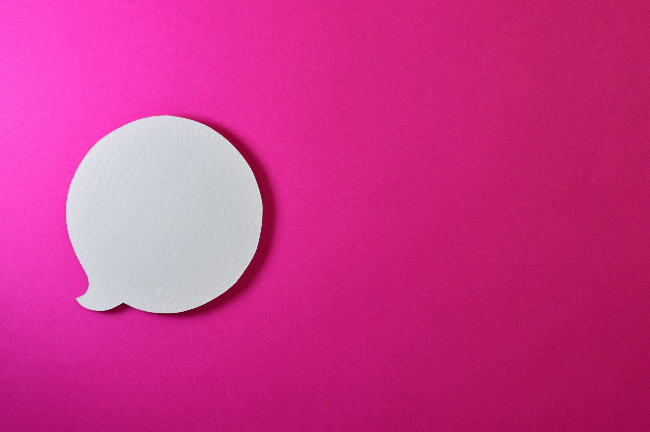 A paper speech bubble against a pink background because communication is an important part of office ethics.