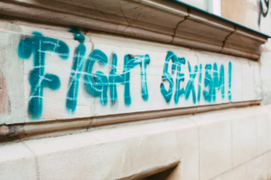 """Fight sexism"" in blue spray paint on a wall because anti-sexism is pervasive part of office ethics."