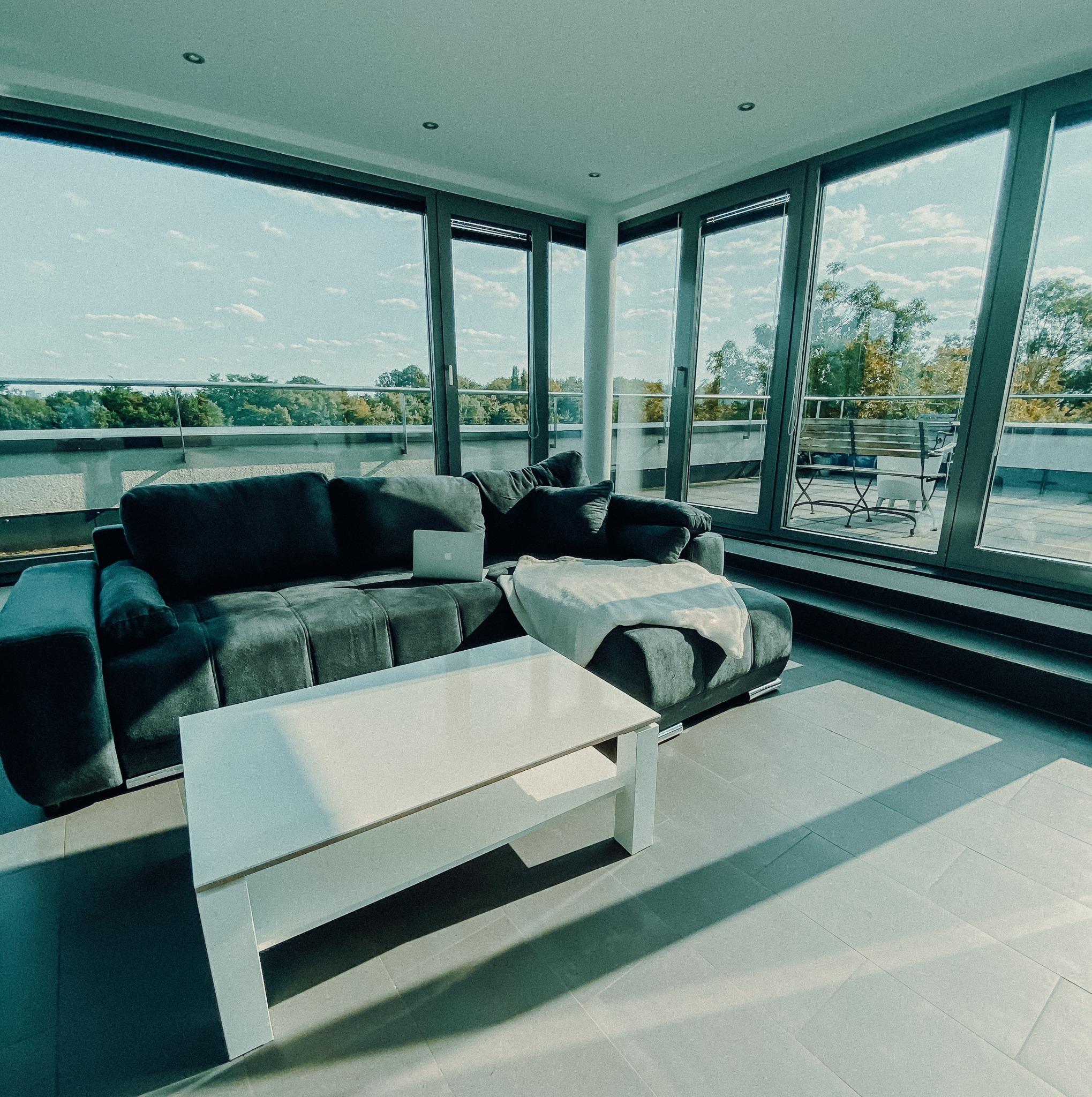 A white and black sofa near a glass window.