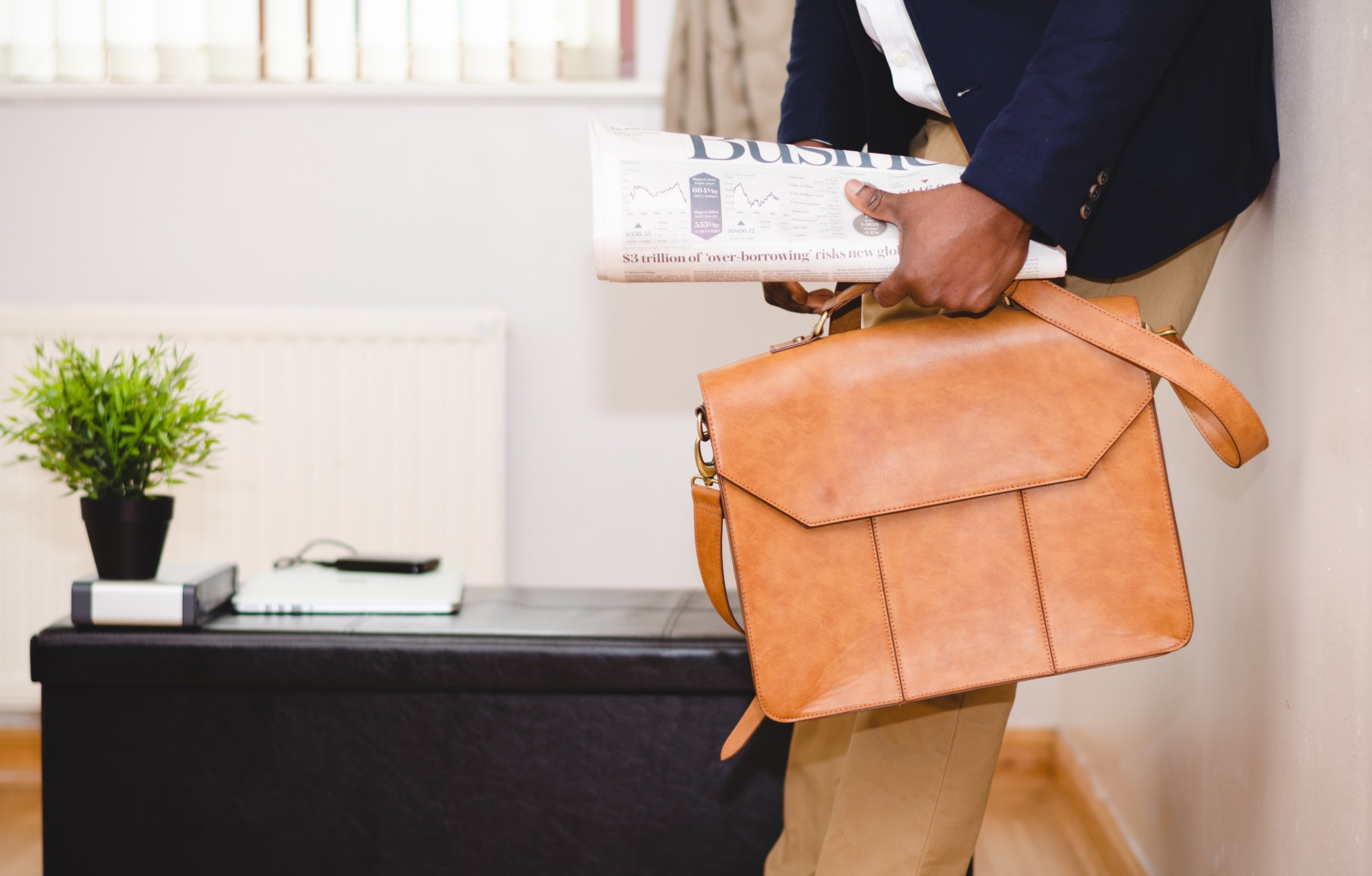Man holding brown leather bag