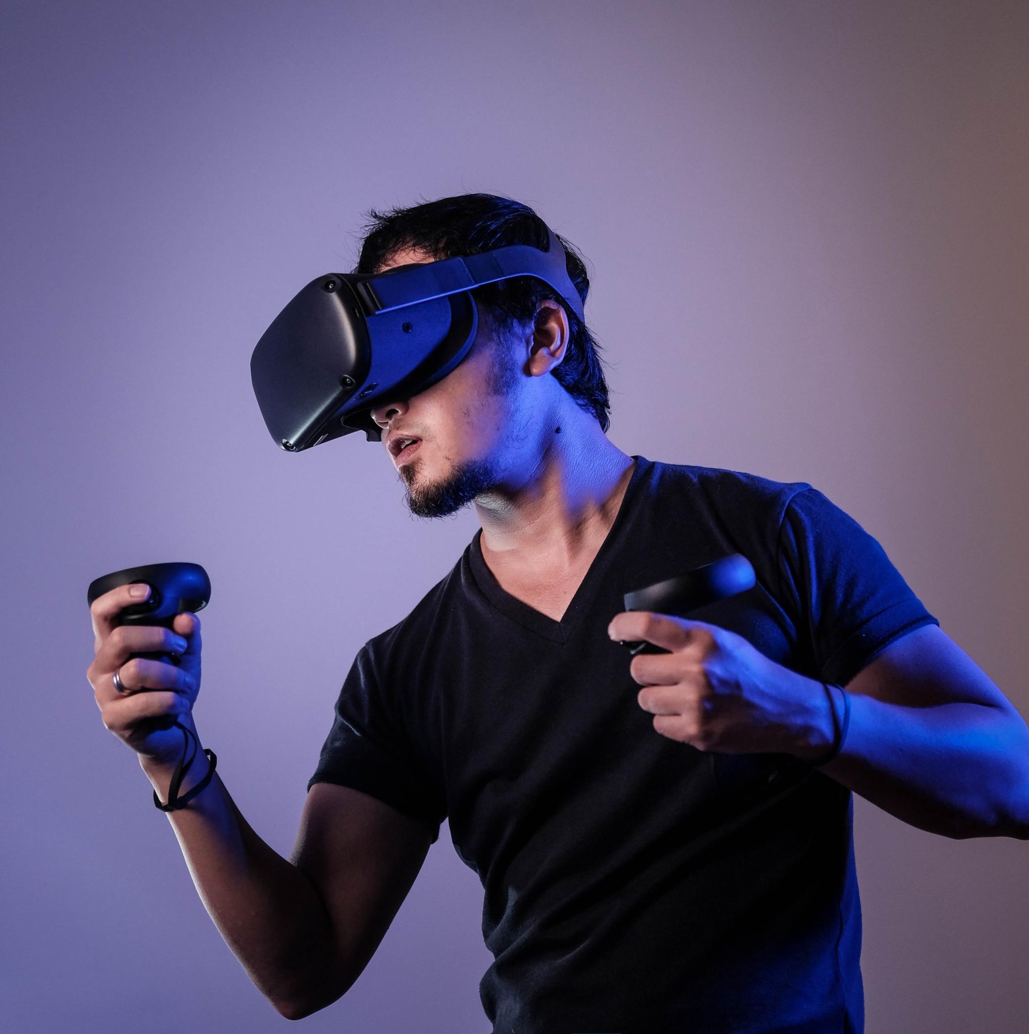 Man in black crew neck wearing black virtual reality glasses.